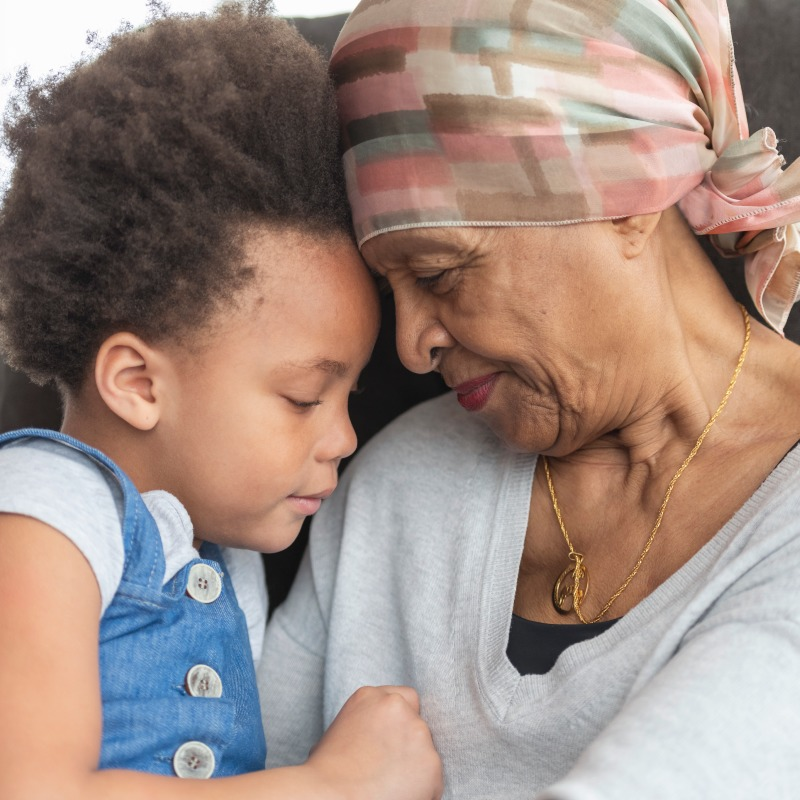 Senior woman with cancer hugging her grandchild